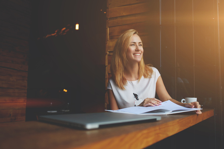 rest day: Beautiful female with cute smile is looking away while relaxing after work on her laptop computer, charming happy woman enjoying rest and good day while sitting alone in modern coffee shop interior Stock Photo