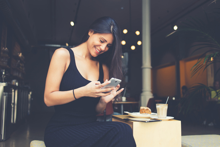 Gorgeous smiling latin woman is typing text message in chat on mobile phone during breakfast in caffe. Young hispter girl is watching funny video on cell telephone whille is sitting in coffee shop