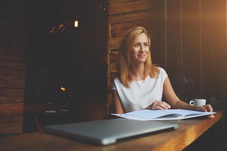 Junge schöne Hippie-Mädchen mit guter Laune ist mit großem Notizblock in Coffee-Shop während ihrer Freizeit Zeit, charmant kaukasischen Frau Ruhe genießen zu sitzen und nach der Arbeit auf ihrem Laptop-Computer ruhen