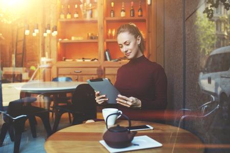 Ver pesar de que la ventana de una mujer que lee el libro electrónico en tableta digital durante el almuerzo en el café cómodo en el interior, el trabajo independiente de sexo femenino bonito en la superficie táctil mientras se está sentado en la cafetería moderna