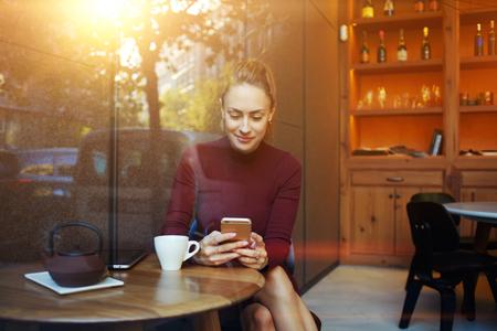 Portré, fiatal, üzletasszony használja mobiltelefon ülve kényelmes kávézóban munka közben szünetet, bájos boldog nő olvasás divat hírek mobiltelefonjára reggeli közben az étteremben