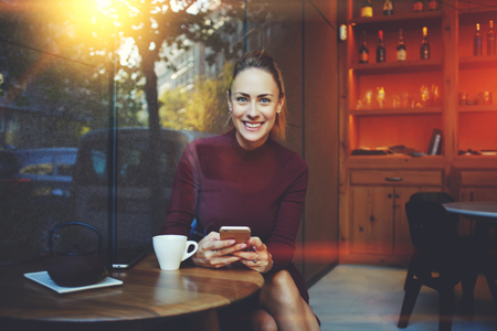 Young woman with beautiful smile posing while sitting with smart phone in modern coffee shop interior, gorgeous cheerful female chatting with her friends via cell telephone during rest in cozy cafe