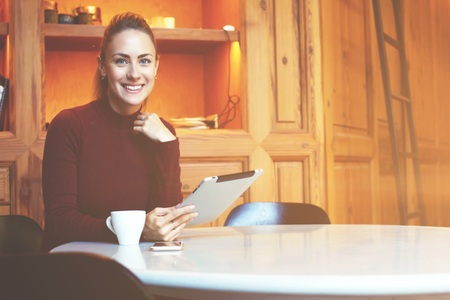 electronic pad: Happy European woman is reading electronic book while is sitting with touch pad in comfortable coffee shop interior, female with cute smile using digital tablet while relaxing during recreation time Stock Photo