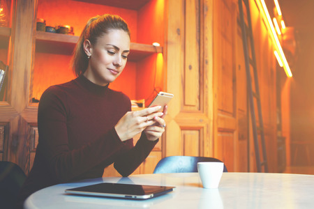loft interior: Young female student is chatting on mobile phone with friend while sitting in modern library interior, gorgeous Caucasian woman using cell telephone while rest in coffee shop during winter holidays