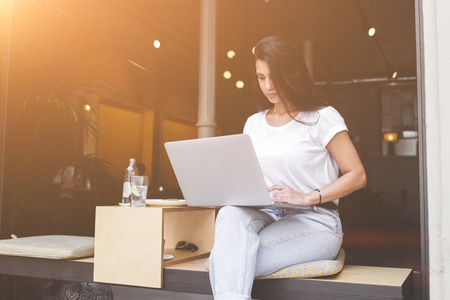 one person: Young female freelancer is working on net-book while breakfast in modern coffee shop with contemporary design. Charming latin woman is connecting to wireless for browsing internet on laptop computer Stock Photo