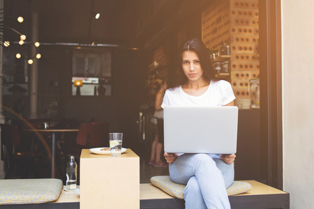 netbook: Young latin woman is sitting with open laptop in modern sidewalk coffee shop. Female freelancer is using net-book for distance work by internet connection.Student hipster girl is learning via computer Stock Photo