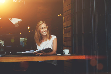 female magazine: Young beautiful cheerful female looking away while sitting with magazine in modern coffee shop interior, happy smiling hipster girl enjoying good day while relaxing in cozy cafe bar after work day