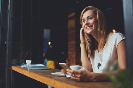 Femmina felice utilizzando smart phone mentre ci si rilassa in un caffè dopo aver camminato durante il suo week-end d'estate, affascinante sorridente vita bassa ragazza ha ricevuto una buona notizia sul telefono cellulare mentre lei seduto in accogliente caffetteria