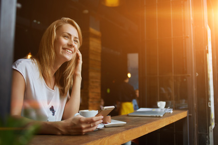 Happy female using smart phone while relaxing in cafe after walking during her summer weekend, charming smiling hipster girl received good news on cell telephone while she sitting in cozy coffee shop
