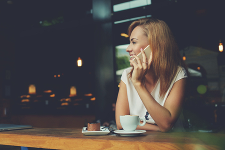 break free: Young happy hipster girl speaking with her friend by mobile phone while relaxing in cozy coffee shop, charming lady with beautiful smile talking on cell telephone while sitting in cafe during lunch