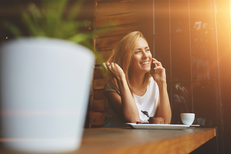 office time: Happy beautiful female with cute smile having cell telephone conversation while sitting in coffee shop during recreation time, smiling woman calling with mobile phone during morning breakfast in cafe