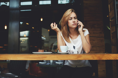 bad mood: Young woman is having unpleasant conversation on mobile phone with her husband, because of jealousy. Concerned female have in bad mood tis talking on cell telephone while sitting alone in coffee shop