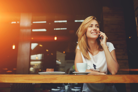 Young charming woman calling with cell telephone while sitting alone in coffee shop during free time, attractive female with cute smile having talking conversation with mobile phone while rest in cafe Archivio Fotografico