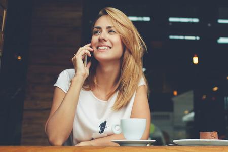 若い魅力的な女性を持つキュートな笑顔とカフェで休憩しながら携帯電話の会話を話して自由時間中に喫茶店で魅力的な女性一人で座って携帯電話 写真素材