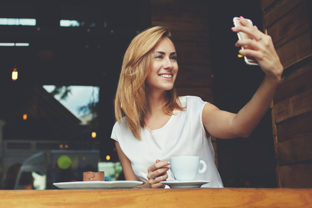 self   portrait: Happy smiling hipster girl making self portrait with mobile phone camera while sitting in modern coffee shop, cheerful woman posing while photographing herself for social network picture, copy space Stock Photo