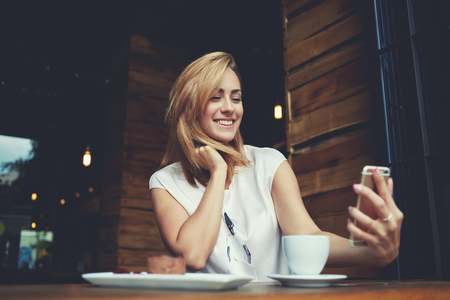 good mood: Young cheerful woman posing while photographing herself on smart phone camera for a chat with her friends, attractive smiling hipster girl making self portrait on cell telephone while sitting in cafe