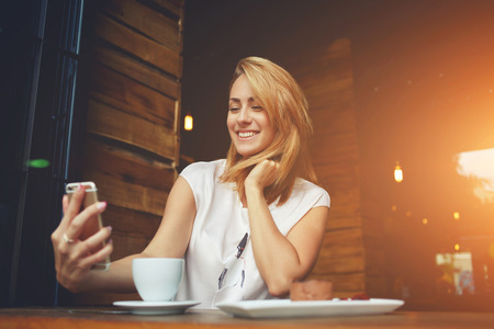Young cheerful woman posing while photographing herself on smart phone camera for a chat with her friends, attractive smiling hipster girl making self portrait on cell telephone while sitting in cafe