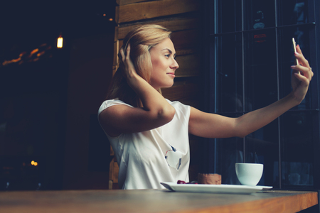 self   portrait: Young gorgeous woman making self portrait with mobile phone camera while sitting alone in modern coffee shop, attractive European female posing while photographing herself for social network picture