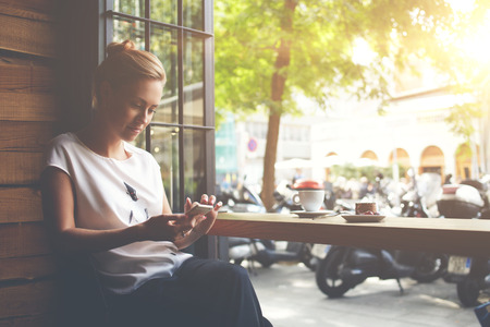 Young gorgeous lady chatting on her smart phone while relaxing in cafe after walking during summer weekend, attractive woman reading text message on cell telephone while sitting in cozy coffee shop