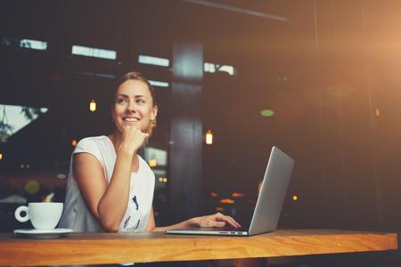 귀여운 미소가 여가 시간 동안 현대 커피 숍 내부에 휴대용 그물 책 앉아 젊은 여성, 랩톱 컴퓨터를 사용하는 매력적인 행복 한 여자 학생은 물론 작업