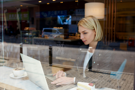 netbook: Young woman freelancer is ordering fly tickets on-line via laptop computer, while is sitting in modern hipster coffee shop interior. Smart female remote programmer is using net-book for distance work Stock Photo