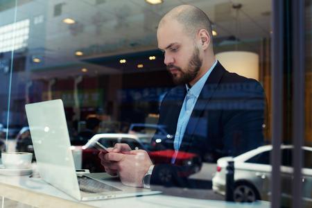 hombre con barba: liderazgo joven hombre de negocios de gran éxito de la empresa está comprobando el estado de la cuenta bancaria a través de la aplicación en el teléfono móvil después de hacer compras en línea a través de ordenador portátil. Rotura de trabajo en la casa de café