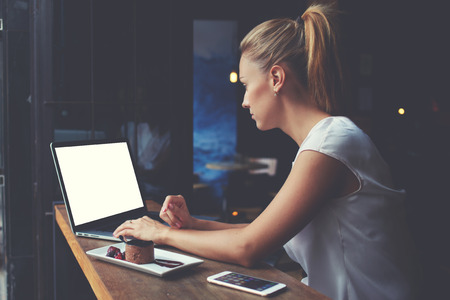 modern girl: Young female student working on net-book with blank copy space screen for your text message or promotional content, cute woman successful freelancer using laptop computer while sitting in coffee shop