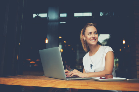 free thinking: Gorgeous cheerful woman freelancer with good mood using laptop computer for distance work during lunch in cafe bar, attractive female with beautiful smile sitting with portable net-book in coffee shop Stock Photo
