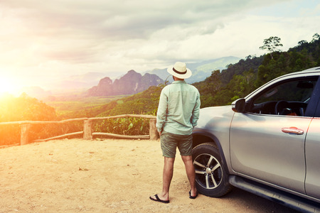 world thinking: Back view of a man is thinking about this amazing world, while is standing on a mountain against jungle view. Young male traveler is enjoying beautiful landscape during road trip on suv in Thailand