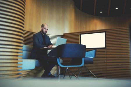wealthy lifestyle: Serious businessman in luxury suit is working on laptop computer, while is sitting in modern co-working space near screen with mock up copy space for your advertising text message or information