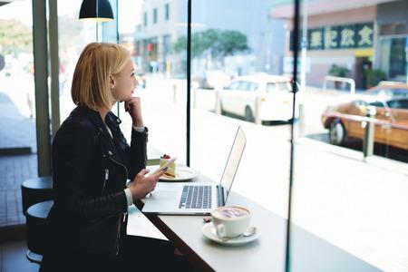 fille Hipster avec un téléphone mobile thoughfull regarder dans la fenêtre, tout en est assis dans inter café moderne à la table avec un ordinateur portable ouvert computer.Woman pigiste est d'utiliser le téléphone cellulaire et net-book