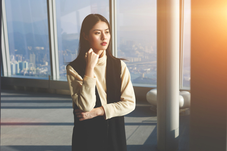 serious meeting: Independent Asian female owner of successful company in China is waiting serious meeting with international partners. Young beautiful hipster girl with trendy look is looking in big skyscraper window