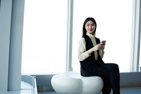 hing: Japanese young female student is using mobile phone, while is waiting the beginning of lectures in modern hing business school. Asian woman sitting in modern interior near copy space for your content