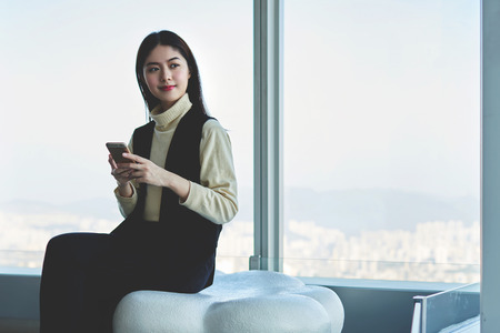 Japanese female student were read in e-mail on mobile phone letter about positive response to a request for admission to the new university in New York. Asian businesswoman sitting in office interior Banque d'images