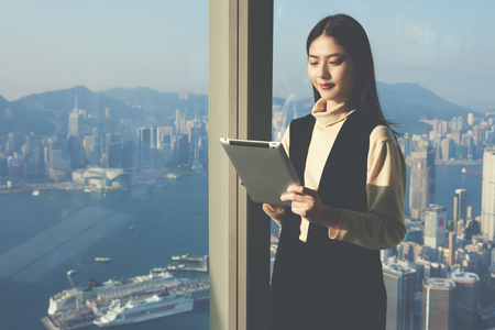 international internet: Young successful businesswoman is reading information in internet via portable touch pad about international partner before meeting with him, while is standing in luxury skyscraper office interior Stock Photo