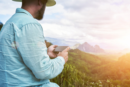 subtropical: Closely of a man wanderer is holding mobile phone with copy space on the screen for young advertising content. Young hipster guy with cell telephone in hands is enjoying amazing subtropical forest