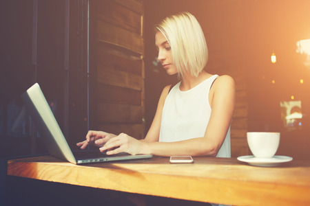 netbook: Young attractive lady keyboarding something on portable net-book while sitting in coffee shop during work break, beautiful smart female student using laptop computer to prepare for the coursework Stock Photo