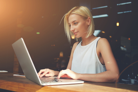 free business: Young charming female freelancer using laptop computer for distance job while sitting in modern coffee shop interior, beautiful Caucasian woman working on net-book during morning breakfast in cafe bar