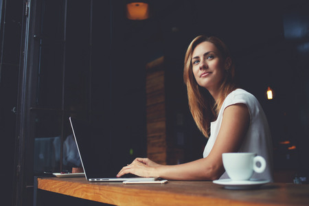 Beautiful Caucasian woman dreaming about something while sitting with portable net-book in modern cafe bar, young charming female freelancer thinking about new ideas during work on laptop computer Standard-Bild
