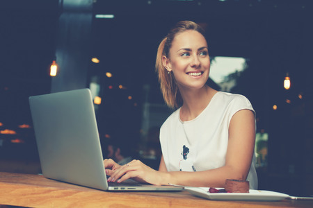 Gorgeous cheerful woman freelancer with good mood using laptop computer for distance work during lunch in cafe bar, attractive female with beautiful smile sitting with portable net-book in coffee shop Stock Photo