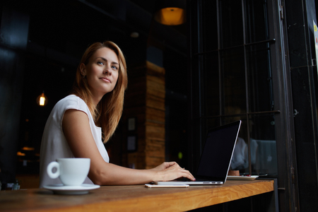 business training: Beautiful Caucasian woman dreaming about something while sitting with portable net-book in modern cafe bar, young charming female freelancer thinking about new ideas during work on laptop computer Stock Photo