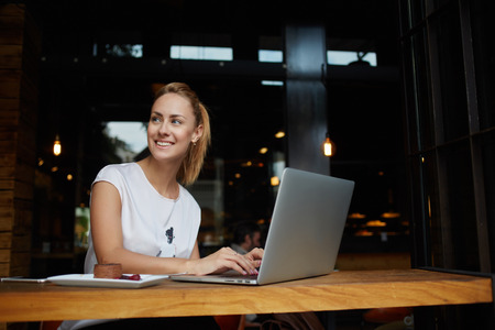 netbook: Gorgeous cheerful woman freelancer with good mood using laptop computer for distance work during lunch in cafe bar, attractive female with beautiful smile sitting with portable net-book in coffee shop Stock Photo