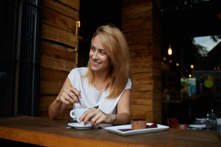 day break: Young woman with beautiful smile looking away while sitting in cafe during coffee break, happy charming hipster girl relaxing in modern cafe, female enjoying good day during morning breakfast in bar