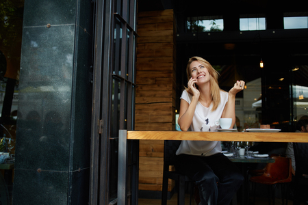Young pretty female with good mood talking on mobile smart phone with her friend while relaxing in cafe, happy woman speaking with cell telephone while sitting in coffee shop during morning breakfast