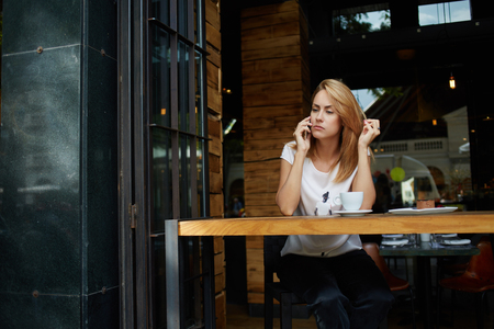 serious face: Upset woman heard the bad news with mobile phone while relaxing after work day in modern coffee shop, charming female with serious face calling with cell telephone during rest in cozy cafe bar