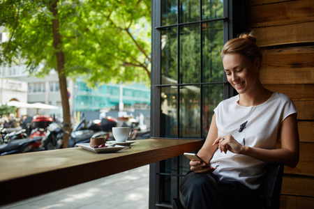 woman  smile: Charming woman with beautiful smile reading good news on mobile phone during rest in coffee shop, happy Caucasian female watching her photo on cell telephone while relaxing in cafe during free time