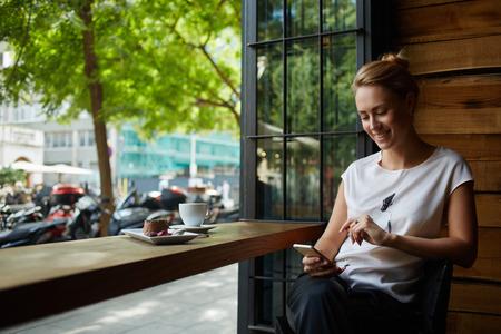 Mujer encantadora con una hermosa sonrisa de leer buenas noticias en el teléfono móvil durante el descanso en la cafetería, feliz hembra caucásica mirando su foto en el teléfono celular mientras se relaja en el café durante el tiempo libre Foto de archivo