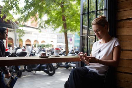 夏の週末の間に魅力的な女性が居心地の良いコーヒー ショップに座って携帯電話でテキスト メッセージを読んで歩いた後カフェでリラックスしなが