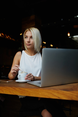 netbook: Young charming dreamy Caucasian woman sitting with portable net-book in cafe during coffee break, beautiful blonde female thinking about something while relaxing after job on her laptop computer