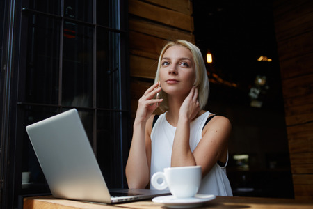 Young attractive female calling with her smart phone while sitting with portable net-book in coffee shop, beautiful blonde female talking on cell telephone while rest after work on laptop computer